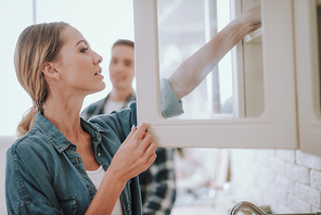 Young woman opening the glass door of the cupboard and putting her hand on the shelf. Man standing on the background