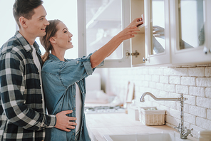 Cheerful loving man standing behind the back of his smiling wife and hugging her while watching her putting cup into the cupboard