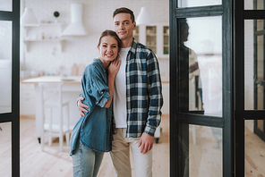 Beautiful couple. Confident young man standing and smiling while his loving wife leaning to him at the kitchen entrance