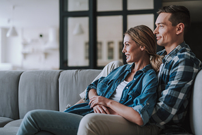 Relaxed young couple hugging on the sofa and looking away with a smile. Copy space on the left side