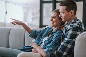 Happy young woman sitting with her husband on the sofa and smiling while watching TV with him and pointing her finger to the screen