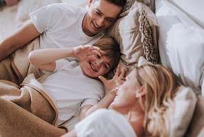 Cheerful kid lying in bed between his parents and having fun while putting hands up pretending being scary