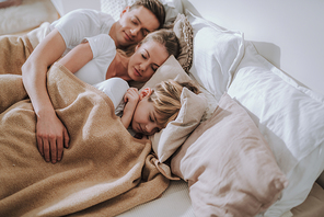 Waist up of man putting arm on his wife and son while sleeping under one blanket in bed with them