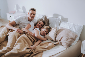 Time to wake up. Cheerful friendly family lying in the bed under one blanket and smiling to the camera