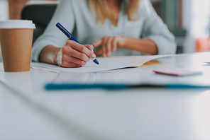 Making notes. Close up photo of the woman at the table with a cup of coffee by her side holding a pen and writing