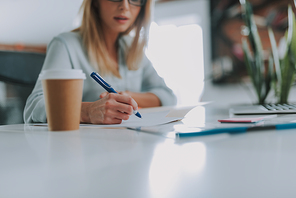 Office worker sitting at the table with a carton cup of coffee by her side and making notes while using a pen