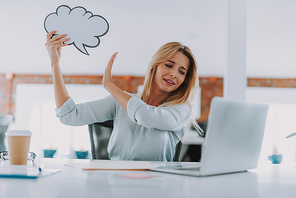 No more thoughts. Emotional young woman looking at the screen of her laptop while putting thought cloud away from her head