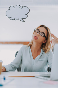 Feeling bored. Office worker sitting at the table with closed eyes and touching her hair while showing tongue and having a thought cloud near the head