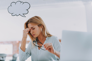 Eye pain. Tired young woman with thought cloud near her head having eye pain at work and taking her glasses off