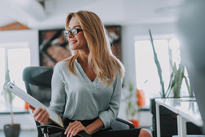 Ready for the meeting. Young happy businesswoman in the office chair turning and smiling while sitting with a clipboard in her hand