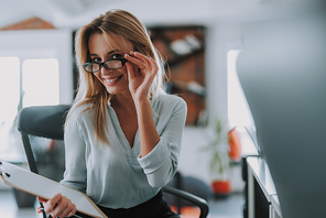 Cute young secretary wearing glasses and touching them while sitting in the office with a clipboard in her hand and smiling