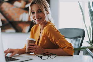 Close up of the smiling young woman in front of the laptop with a cup of coffee in her hand and glasses on the table