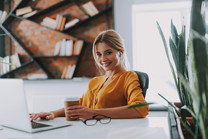 Cheerful confident businesswoman sitting at the table in a modern light office with a laptop and a cup of coffee