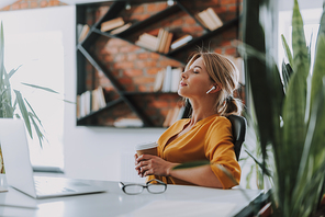 Time to relax. Young businesswoman sitting in the chair at her workplace and closing her eyes while holding a cup of coffee and listening to music