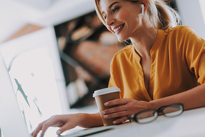 Cheerful woman being at her workplace with a cup of coffee and smiling while using wireless earphones and modern laptop