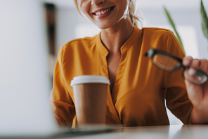 Close up photo of the carton cup of coffee standing in front of the smiling woman in orange blouse