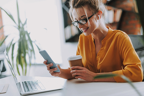Smiling lady with a cup of coffee in her hand using wireless earphones while looking at the screen of the modern smartphone