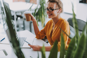 Positive office worker sitting in front of the table and smiling while having smartphone and a cup of hot coffee
