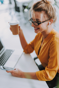 Cheerful young woman in an orange blouse sitting at the office table with wireless earphones in her ears and smiling while enjoying her coffee