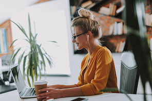 Side view of the busy woman looking at the screen of her laptop and smiling while touching a carton cup of coffee by her side