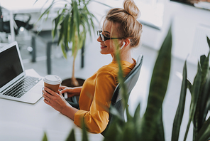 Beautiful blonde woman at her workplace surrounded by plants. Cup of coffee in her hand and laptop on the table
