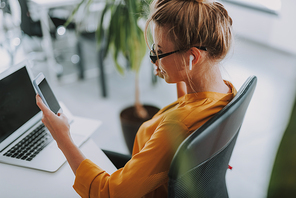 Businesswoman in an orange blouse sitting in the office with a laptop in front of her and having wireless earphones while using smartphone