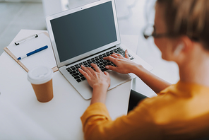 Copy space photo of the modern laptop on the table and hands of woman on the keyboard