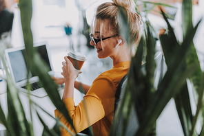 Close up of the woman listening to music in wireless earphones while sitting in the office with plants and drinking coffee