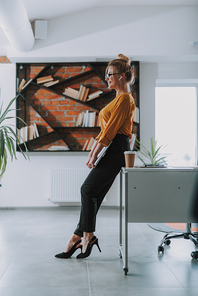 Full length of the young smiling businesswoman standing next to her office table with a modern laptop in her hands
