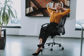 Calm young businesswoman listening to music in wireless earphones while relaxing in the office chair with hands behind her head
