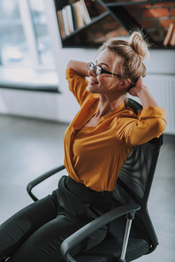 Young businesswoman in blouse and trousers sitting comfortably in her office chair with hands behind her head and smiling