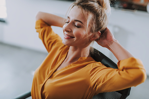Calm young lady in orange blouse having her eyes closed and putting hands behind her head while relaxing on the chair