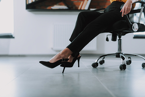 Close up photo of the woman in black trousers sitting in the office and having high heeled shoes on her feet