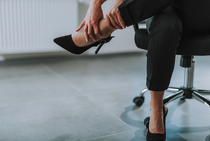 Pain in foot. Close up of the woman in black trousers and high heeled shoes touching her foot