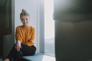 Waist up of a positive young lady in elegant clothes sitting on the window sill at daytime and smiling