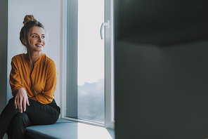 Positive young woman smiling and looking into the distance while sitting on the window sill. Copy space on the right side