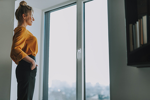 Young blonde woman in orange blouse having her hands in the pockets and smiling while looking out of the window